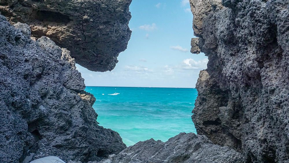 View of Ocean Framed in Rocks at Tropic Breeze Beach